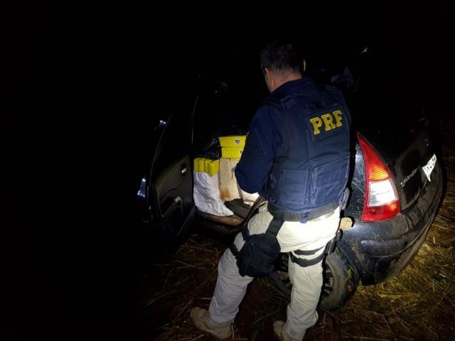 Policial observa fardos de maconha em C3 abandonado na BR-463 (Foto: Divulgação)